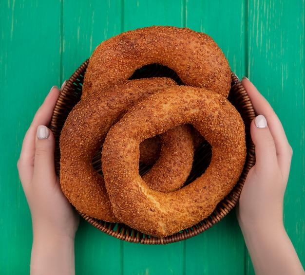 Vista dall'alto delle mani femminili che tengono un secchio con bagel turco tradizionale su un fondo di legno verde