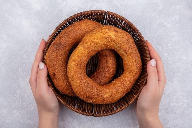 Vista dall'alto delle mani femminili che tengono un secchio con bagel turco tradizionale su una priorità bassa bianca
