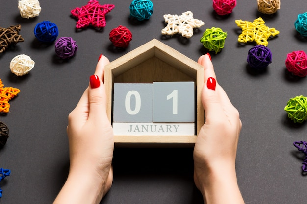 Top view of female hands holding calendar on black background