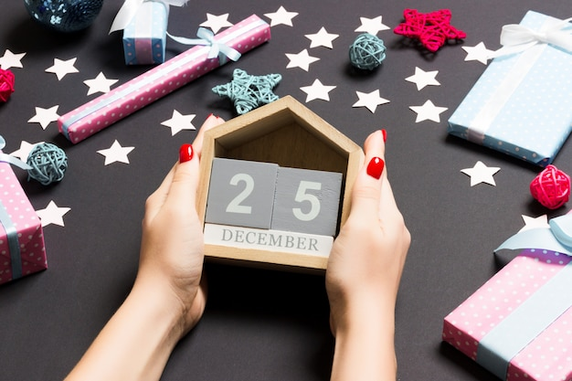 Top view female hands holding calendar on black . the twenty fifth december. holiday decorations. christmas time