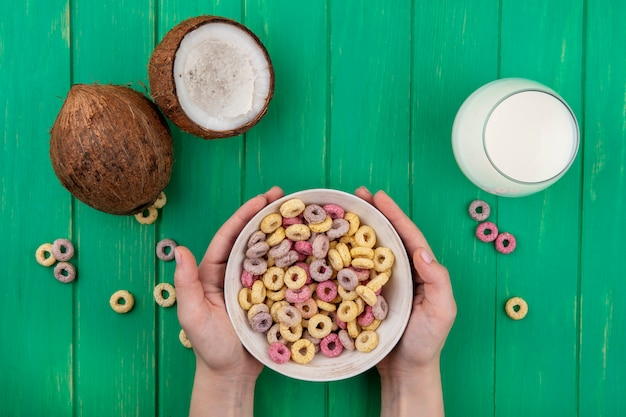 Top view of female hands holding cereals on white bowl with coconuts and a glass of milk on green
