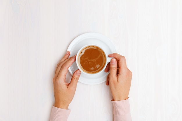 Top view on female hands holding a cup of coffee with milk at the table.