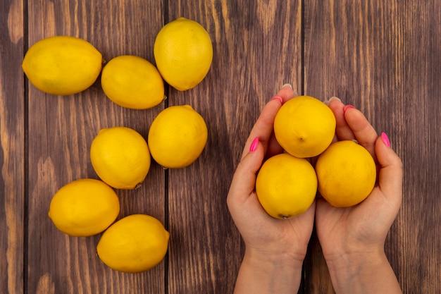 Vista dall'alto delle mani femminili che tengono i limoni freschi su un fondo di legno