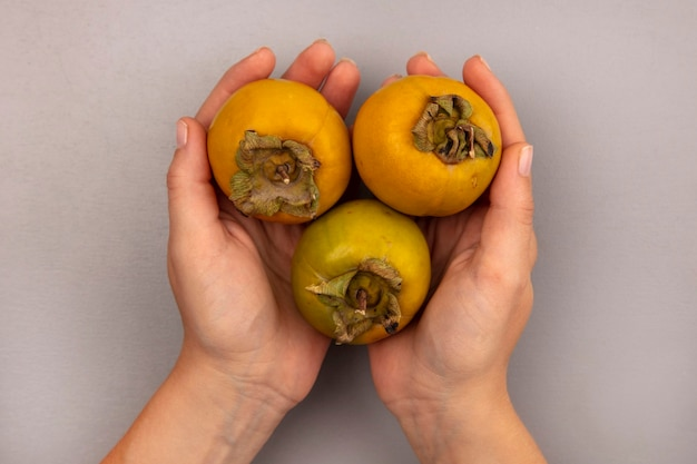 Top view of female hands holding fresh organic persimmon fruits