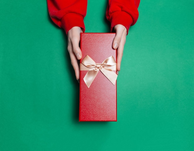 Top view of female hands holding gift box on surface of green color