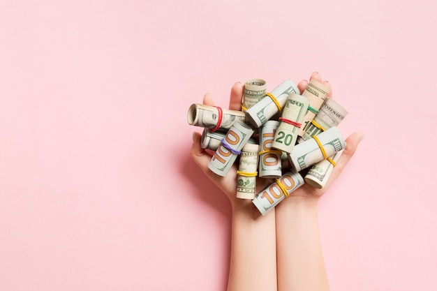 Top view of female hands holding a lot of rolled up dollar banknotes on colorful background. poverty concept. credit concept