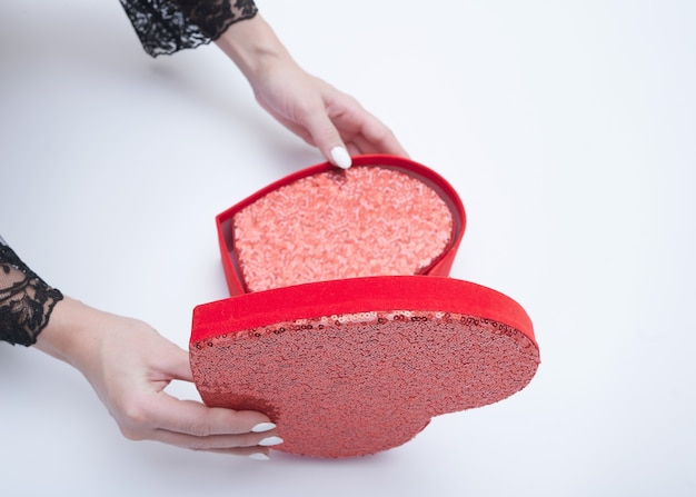 Top view of female hands holding open red gift box on white background
