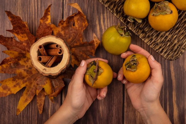 Top view of female hands holding persimmon fruits with cinnamon sticks on a wooden jar with leaves on a wooden table