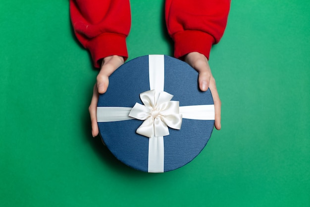 Top view of female hands holding round blue gift box with white bow on surface green color