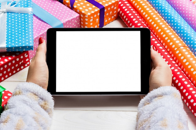 Top view of female hands holding a tablet on wooden christmas made of gift boxes and rolled up wrapping paper.