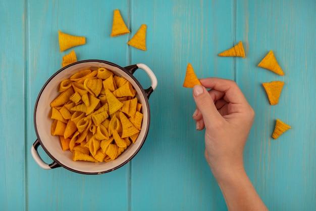 Vista dall'alto delle mani femminili che tengono gustosi spuntini di mais a forma di cono con una ciotola di snack di mais su un tavolo di legno blu