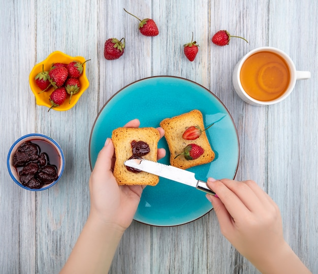 Top view of female hands holding toasted bread with strawberry jam over a blue plate with fresh strawberries on a yellow bowl on a grey wooden background