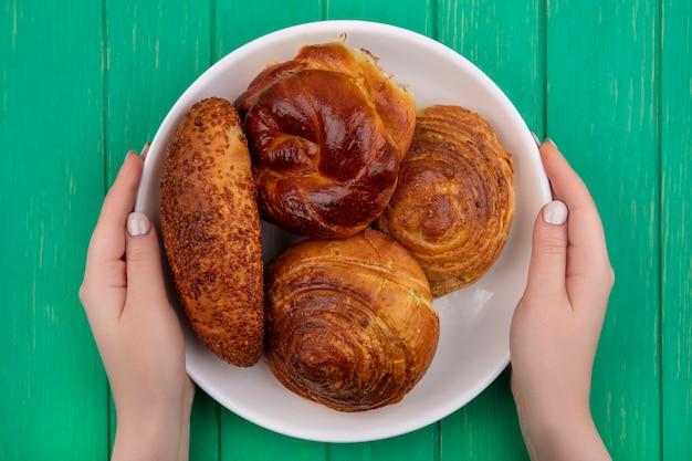 Vista dall'alto delle mani femminili che tengono un piatto bianco con i panini su un fondo di legno verde