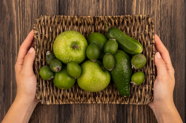 Top view of female hands holding a wicker tray of fresh fruits such as green apples feijoas limes on a wooden surface