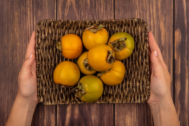 Top view of female hands holding a wicker tray of fresh persimmon fruits on a wooden table
