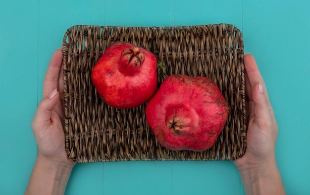 Vista superiore delle mani femminili che tengono il vassoio di vimini con melograni freschi rossi su sfondo blu