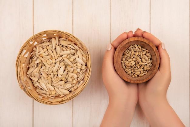 Vista dall'alto delle mani femminili che tengono una ciotola di legno con semi di girasole sgusciati salati saporiti con semi di girasole su un secchio su un tavolo in legno beige