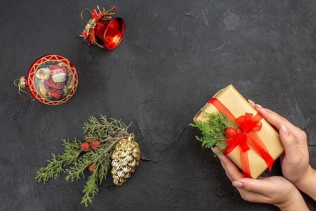 Top view female hands holding xmas gift in brown paper tied with red ribbon xmas tree ornaments on dark background