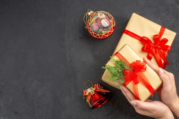 Top view female hands holding xmas gift in brown paper tied with red ribbon xmas tree toys on dark background free space