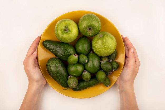 Vista dall'alto delle mani femminili che tengono un piatto giallo di frutta fresca come mele feijoas e avocado su una superficie bianca