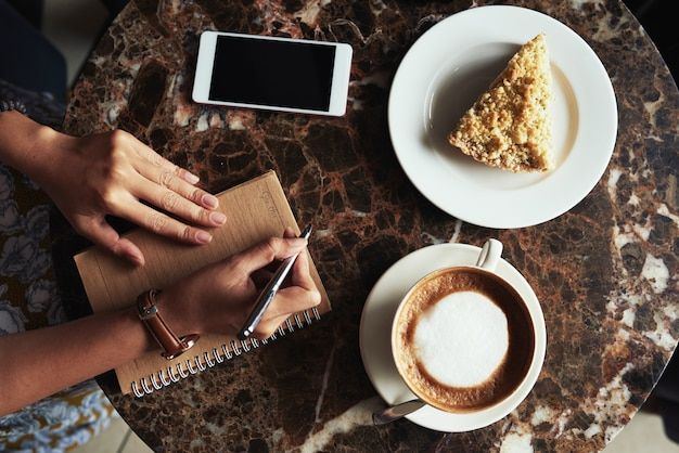 Top view of female hands making notes at a coffee and dessert break