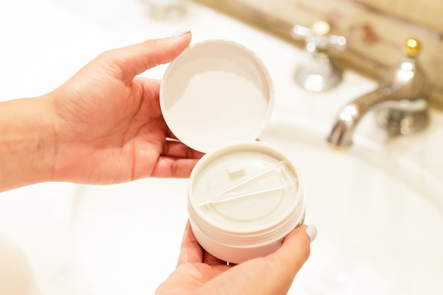 Top view of female hands opening a jar with eye patches in the bathroom.