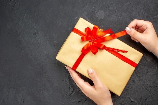 暗い背景の空き領域に赤いリボンと茶色の紙でクリスマスプレゼントを開く上面図女性の手