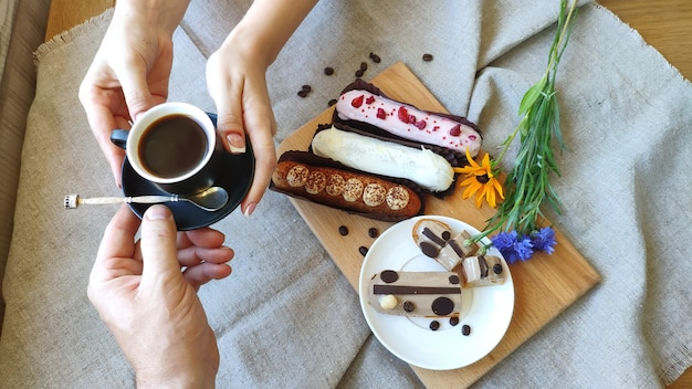 Top view female hands pass a cup of black coffee to a man against the background of served eclairs