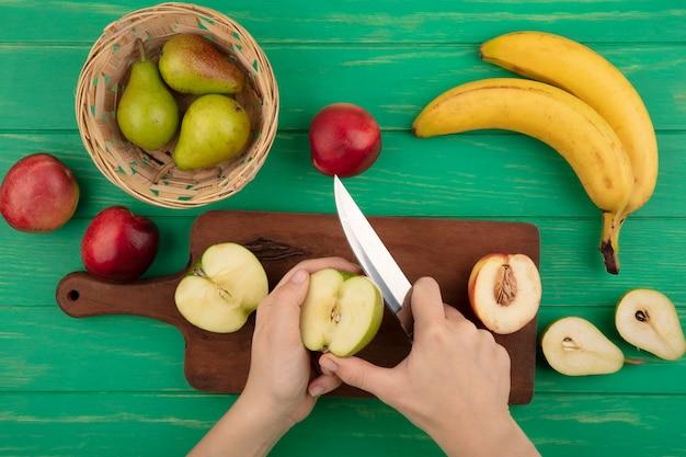 Vista dall'alto delle mani femminili che affettano la mela con il coltello e mezza mela e pesca sul tagliere con pere nel cestino e banane pesche e mezza pera tagliata su sfondo verde