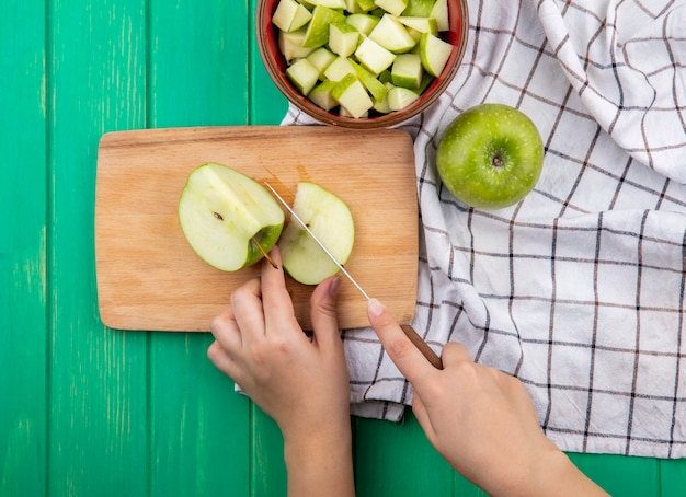 Top view of female hands slicing green apple on wooden kitchen board on red bowl of chopped apples and cloth