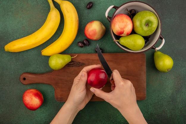 Vista dall'alto delle mani femminili affettare la pesca con il coltello sul tagliere e banana pera uva mela su sfondo verde