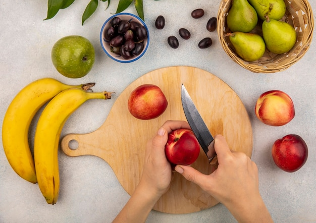 Top view of female hands slicing peach with knife on cutting board and grape pear banana apple with leaves on white background