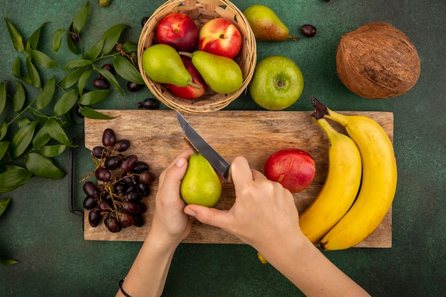 Top view of female hands slicing pear with knife and banana peach grape on cutting board and pear apple cococnut with leaves on green background