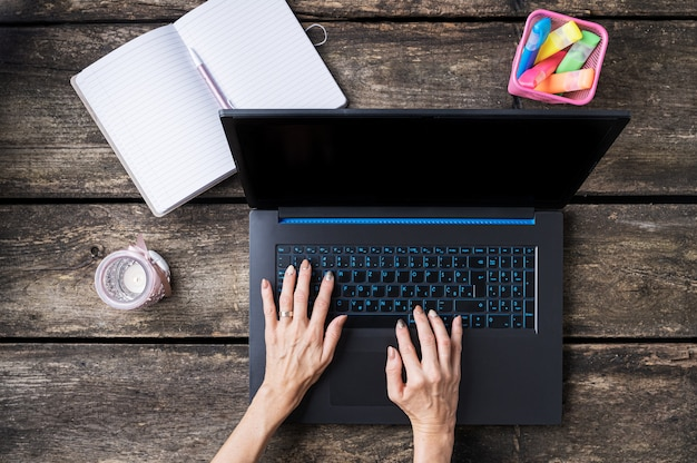 Top view of female hands typing on laptop computer with candle, colorful markers and open notepad beside it on a rustic wooden desk.