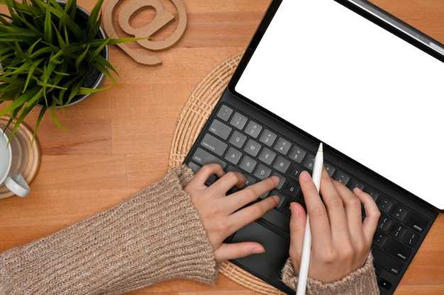 Top view of female hands typing on tablet keyboard on simple wooden workspace clipping path