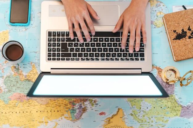 世界地図上のラップトップを使用して平面図の女性の手が次の旅行目的地を予約