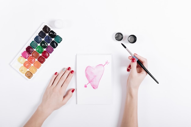 Top view of a female hands with red manicure draw the watercolor heart in notebook