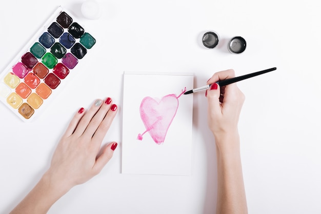 Top view of a female hands with red manicure painted watercolor heart in notebook