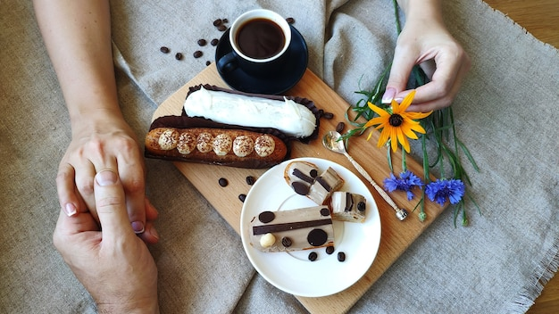 Top view of female and male hands holding each other near a cup of black coffee and served eclairs