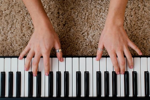 Vista dall'alto del musicista femminile che suona la tastiera del pianoforte