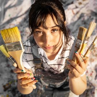 Vista dall'alto della pittrice con i pennelli
