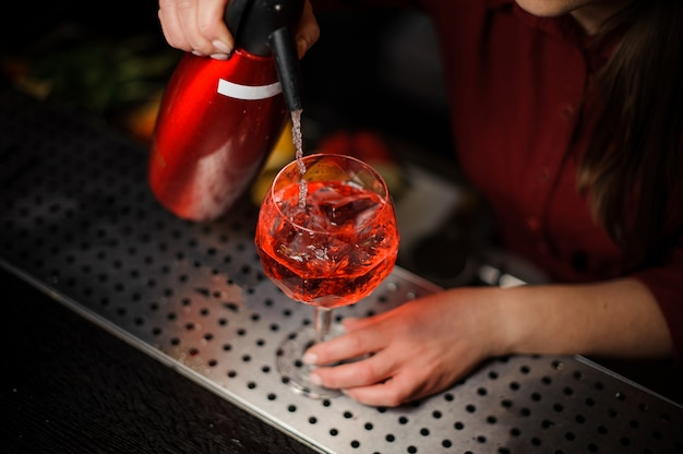 Top view of female parman pouring soda into a glass making an aperol syringe cocktail
