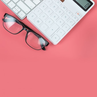 Top view female workplace, computer keyboard, white calculator and glasses on a bright pink background.