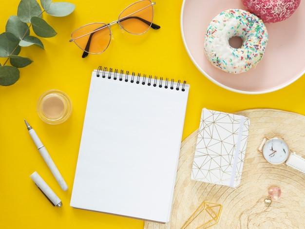Вид сверху женский завтрак на работе. плоский спиральный макет ноутбука, канцелярские товары и пончики на желтом фоне