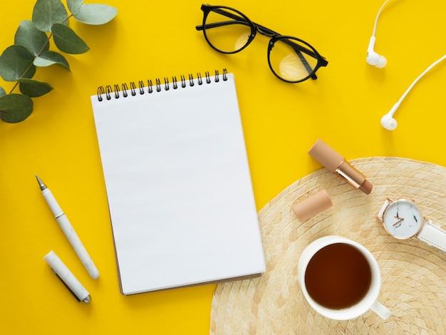 Вид сверху женское рабочее место, вид сверху. очки, спиральный блокнот, чай и эвкалипт на желтом фоне. копировать пространство, вид сверху