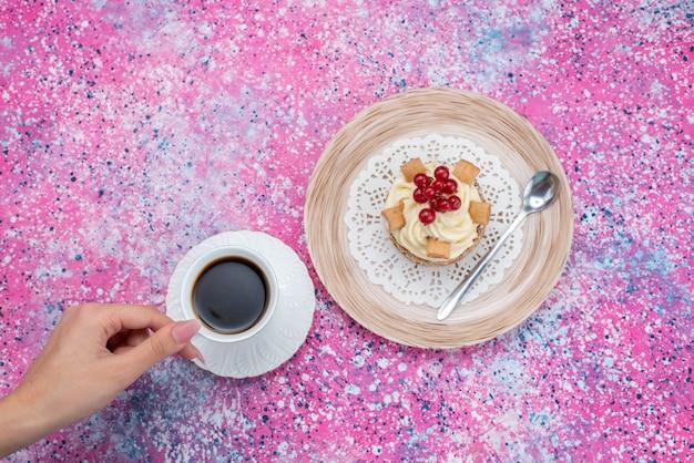 Вид сверху femlae пьет кофе со сливочным пирогом на цветном фоне торт кремового цвета выпечка теста