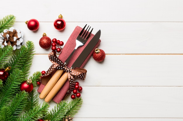 Top view of festive cutlery on new year wooden background. christmas decorations with empty space. holiday dinner concept
