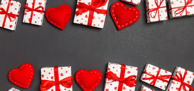 Top view of festive gift boxes and red textile hearts black banner background