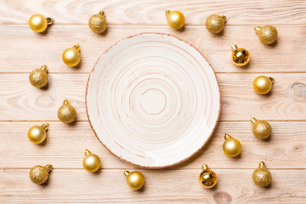Top view of festive plate with golden baubles on wooden surface
