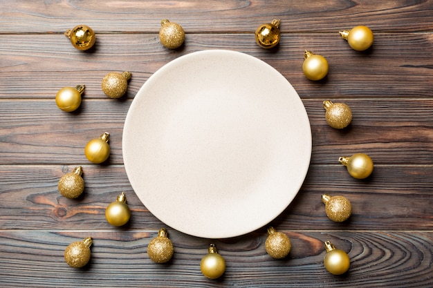 Top view of festive plate with golden baubles on wooden surface.